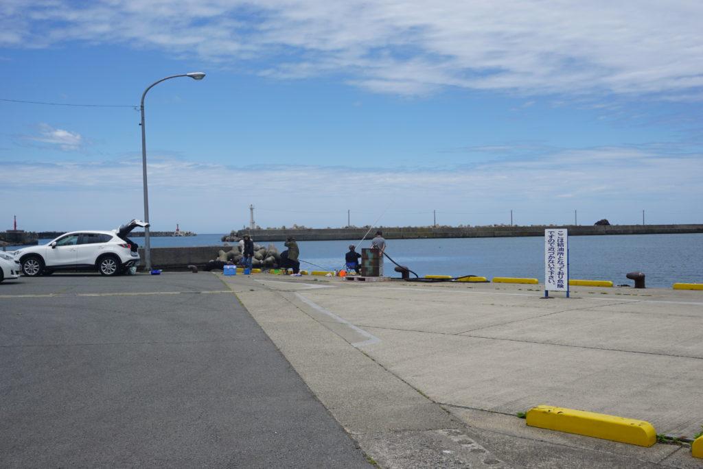 漁港前で釣りをする人々