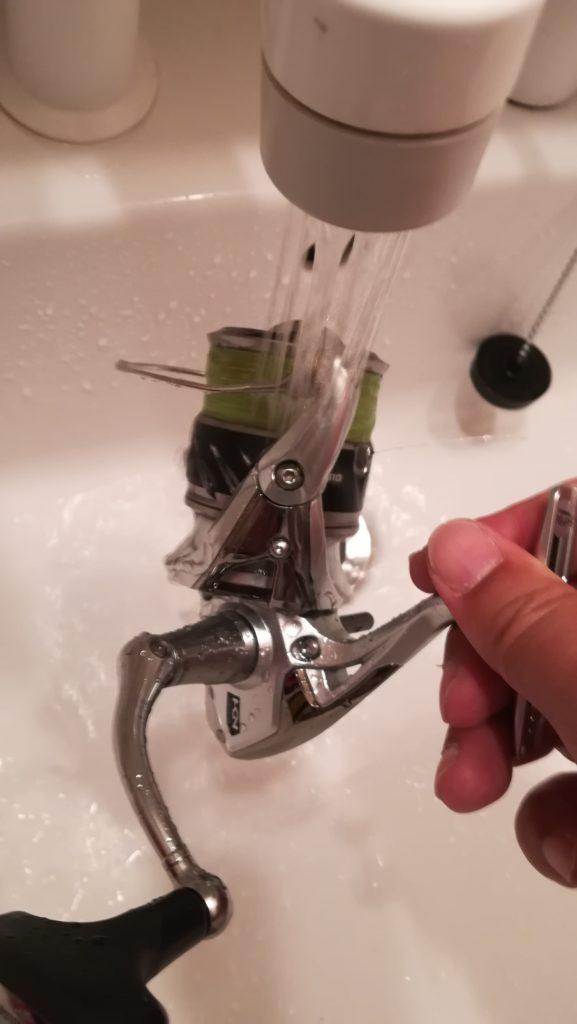 スピニングリールをシャワーで水洗いする様子